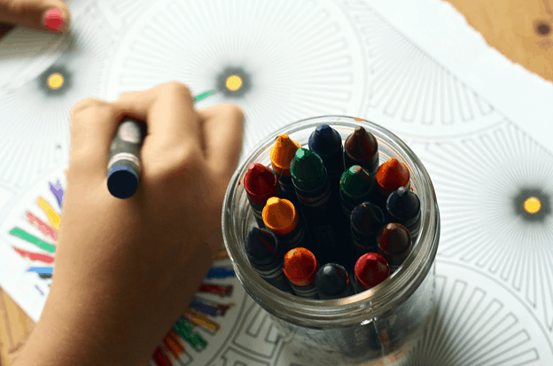 A top view of a cup filled with crayons and on the left a child's hand coloring with a green crayon.