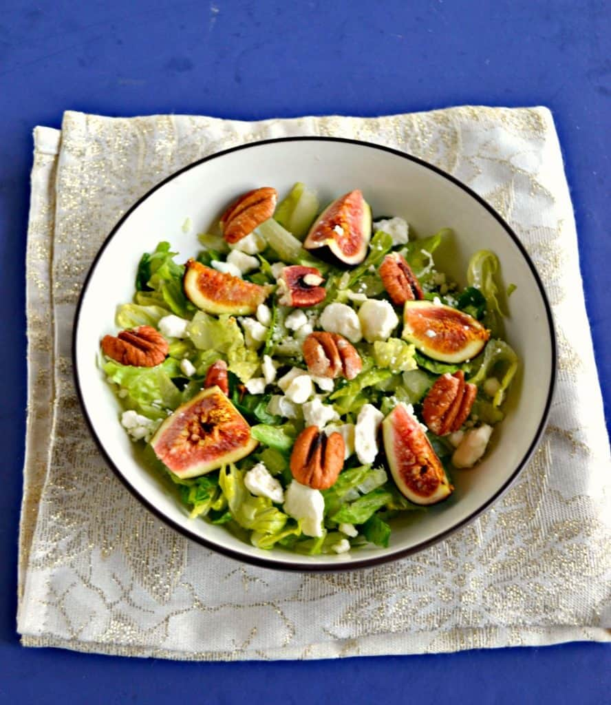 A large bowl filled with mixed greens and topped with ripe pink figs, crumbled white cheese, and pecan halves on a sparkly white background.