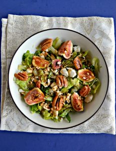 A large bowl filled with mixed greens and topped with ripe pink figs, crumbled white cheese, and pecan halves drizzled with balsamic vinaigrette on a sparkly white background.