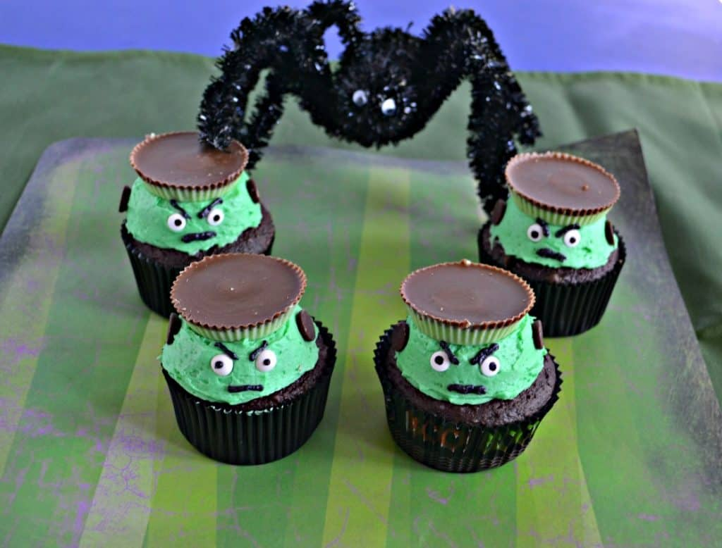 Four Frankenstein Cupcakes with green frosting, edible eyes, and a peanut butter cup hat sitting on a green striped background with a huge spider towering over them in the background.