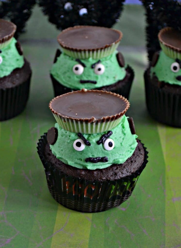 Two Frankenstein Cupcake sitting one behind the other with green frosting, angry eyebrows, edible google eyes, and a peanut butter hat sitting on a green striped background.