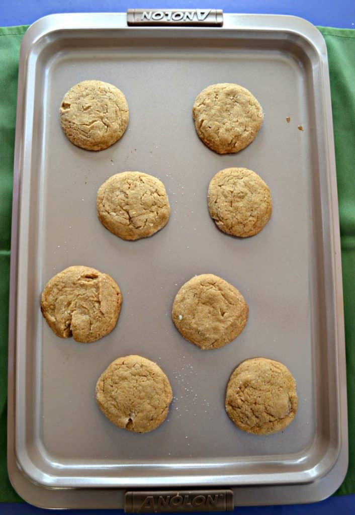 A cookie sheet with 4 rows of 2 cookies in each row. The cookies are brown ginger cookies.