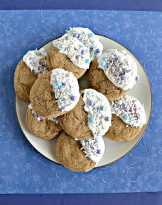 A white plate piled high with brown ginger cookies that are all dipped in white chocolate on the right half of the cookies and sprinkled with white, silver, and blue sprinkles on a blue background.