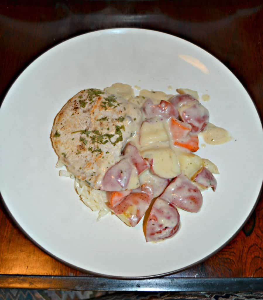 A white plate with a pile in the middle that is onions, red skin potatoes, and carrots with a pork chops on top all in a white gravy.