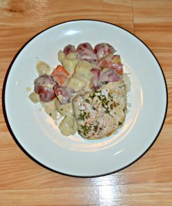 A white plate with a single browned pork chop on it along with red skinned potatoes and carrots in a white gravy.