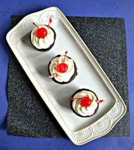 A top view of a white platter with three chocolate cupcakes on it with white frosting and a cherry on top on a sparkly black background.