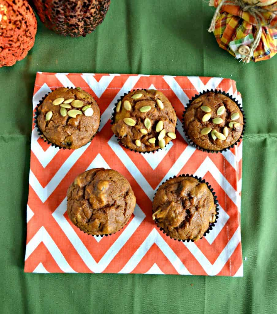 Two rows of muffins, the bottom row has two muffins, the top row has three muffins topped with pepitass and they are on an orange and white place mat on a green background. There are two glitter pumpkin on the top left and a squat scarecrow on the top right.