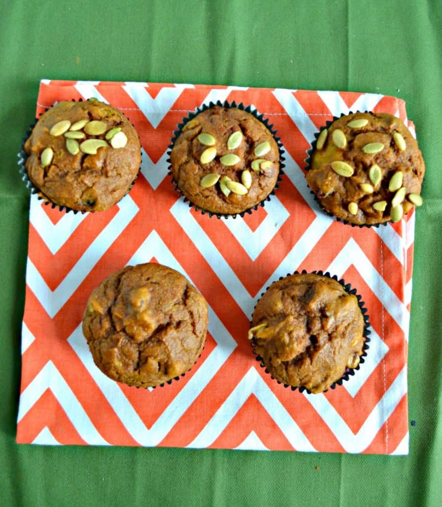 A top view of two rows of muffins, the bottom row has two muffins, the back row has three muffins topped with pepitass and they are on an orange and white place mat on a green background.
