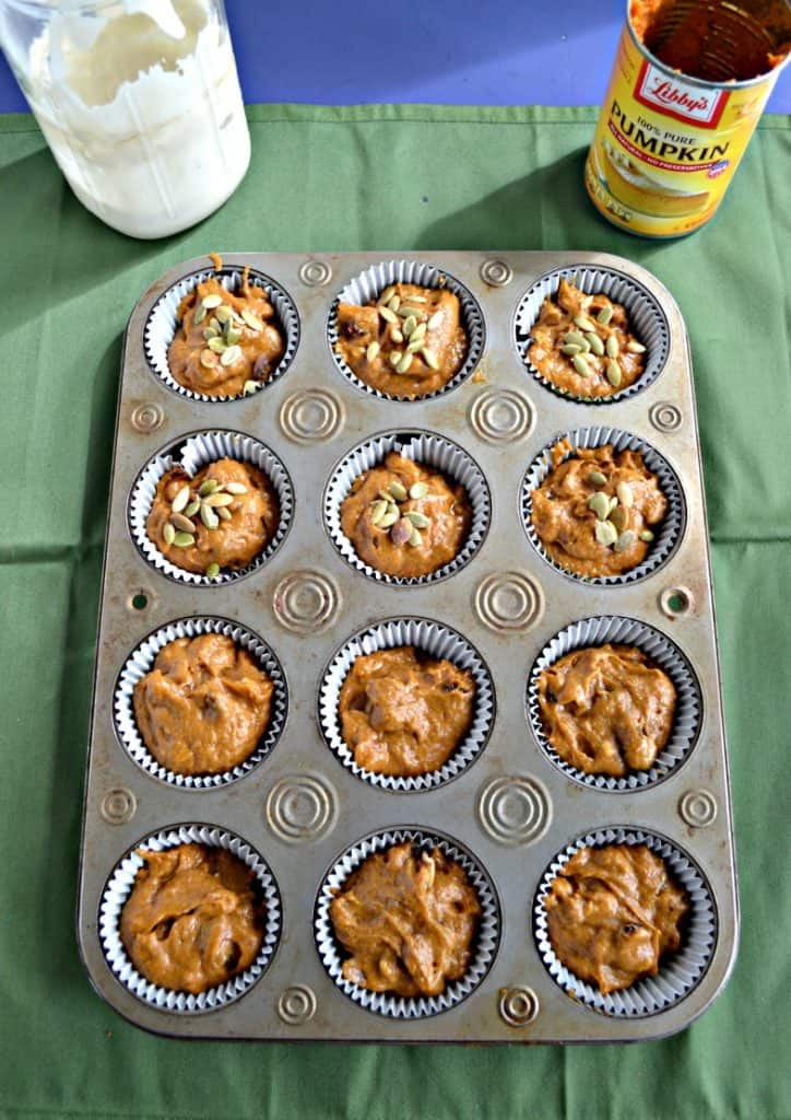 A muffin tin filled with pumpkin batter. The top 6 are topped with pepitas. On the top right is an empty can of pumpkin and on the top left in a jar of sourdough starter.