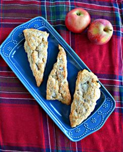A blue platter with three large, golden brown scones on it on a red plaid background with two apples in the back right corner.