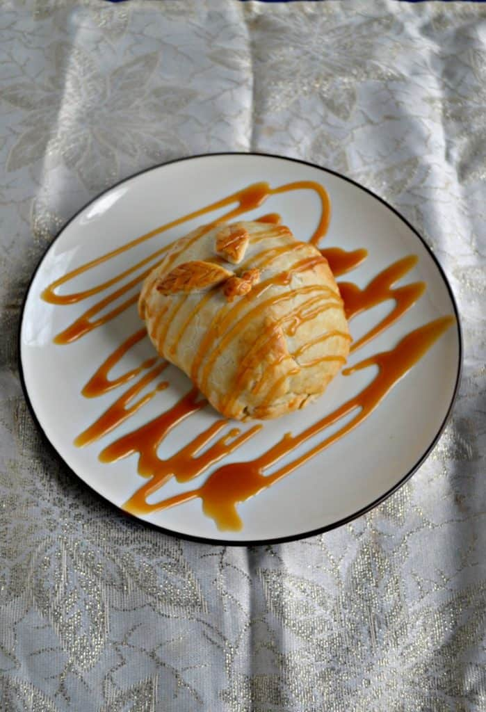 A plate with a golden brown pie dough wrapped pear the has two crust leaves on top that is drizzled with caramel sauce on a white background.