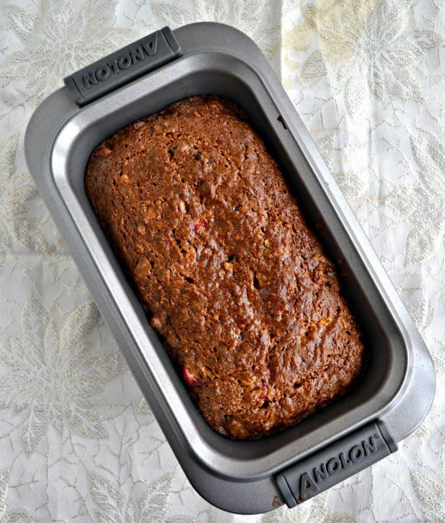 A silver pan filled with a dark brown quick bread on a white and silver background.