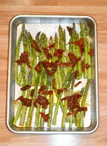 A silver sheet pan with green asparagus spears on it sprinkled with red sun driedd tomatoes and white feta cheese.