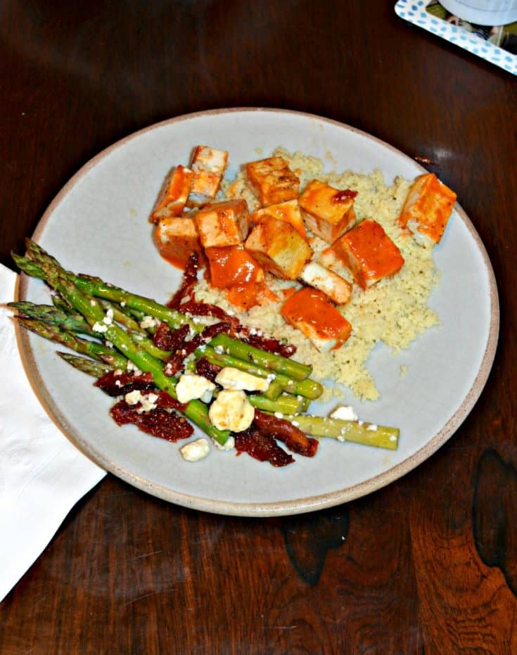 A plate with couscous on the upper right corner and bright orange tofu with asparagus in the lower left corner topped with red tomatoes and white feta cheese,