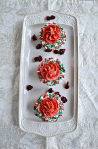 A white platter with three cupcakes on it. Each cupcake has a white ring of frosting with sprinkles on it with red frosting piped in the middle on a white background.