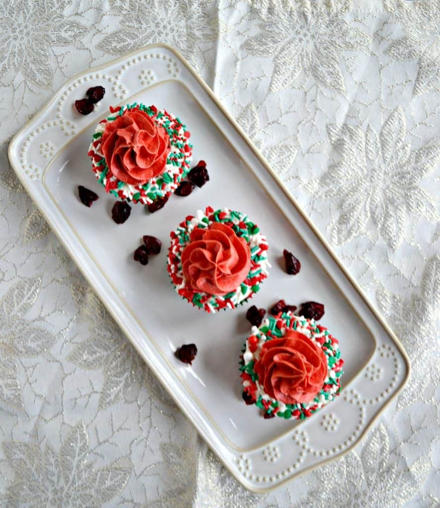 A white platter sitting diagonally with three cupcakes on it. Each cupcake has a white ring of frosting with sprinkles on it with red frosting piped in the middle on a white background.