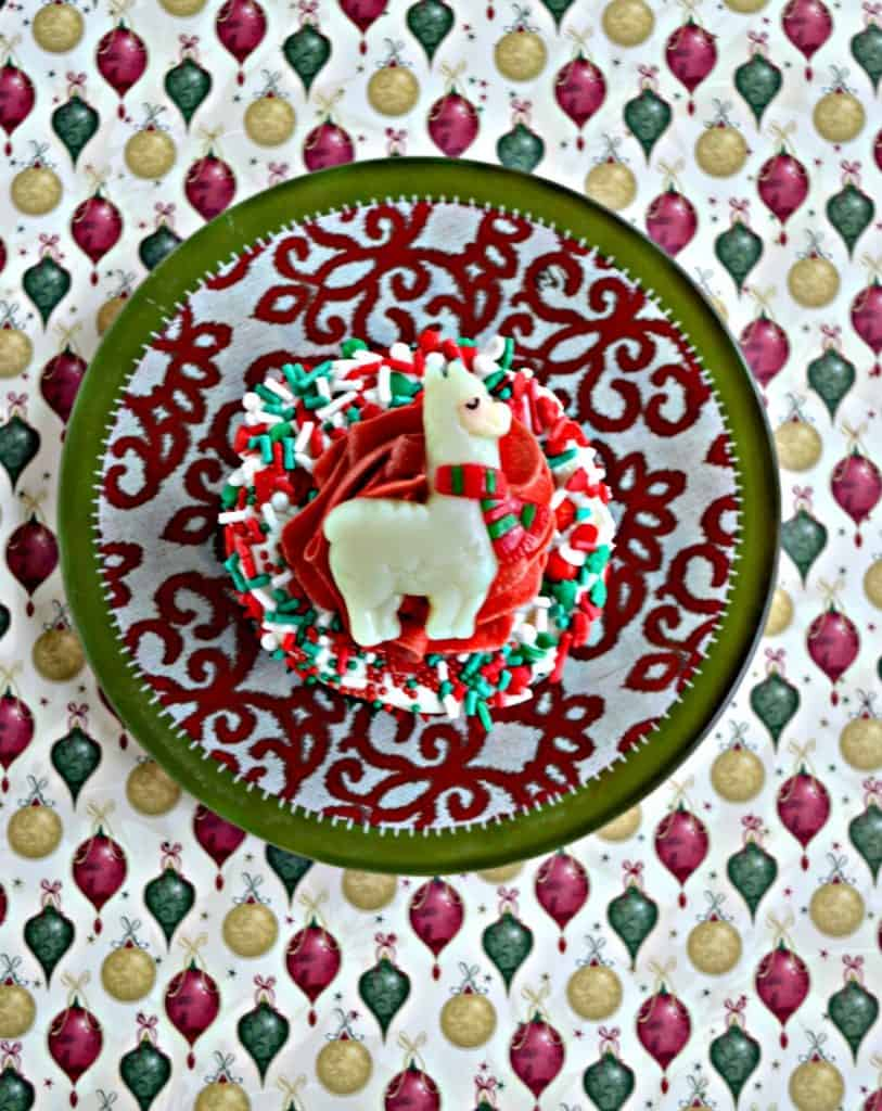 A red, white, and green circular plate with a cupcake in the middle. The cupcake has white frosting and sprinkles around the edges, red frosting in the middle, and a candy llama in the middle.