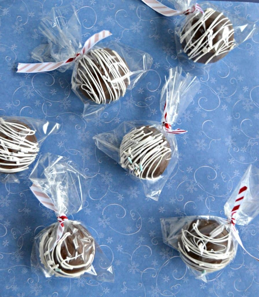 A blue background with six hot chocolate spheres drizzled with white chocolate, wrapped in plastic bags with red and white ribbon tying them, spread out over the blue backdrop.