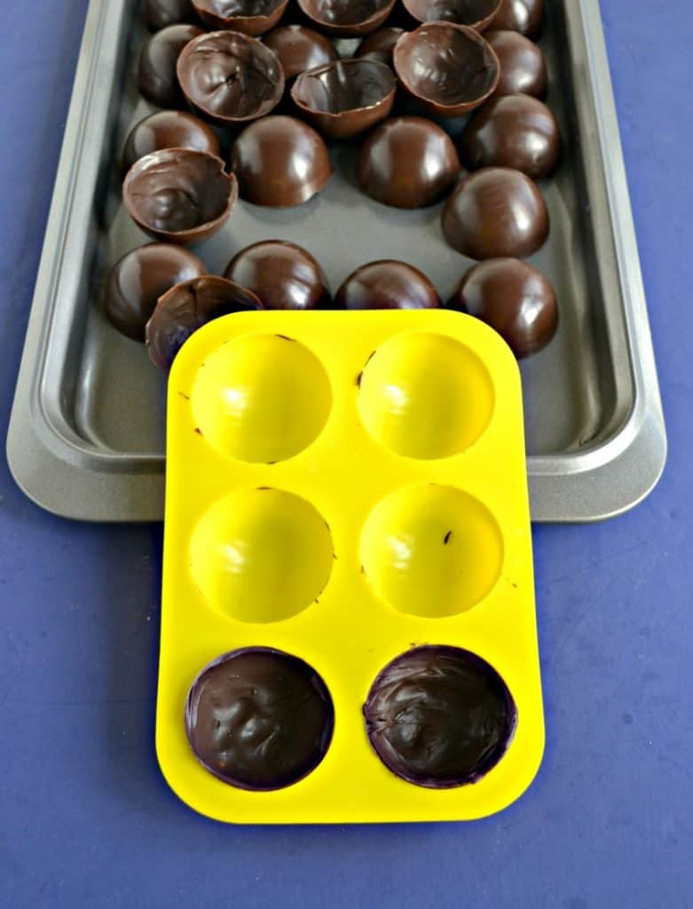 A baking sheet filled with chocolate spheres with a yellow silocone mold sitting upright on it with two circles filled with chocolate.