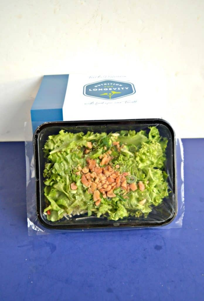 A salad in a black box leaning against a stack of white boxes on a blue background.