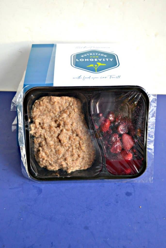 A black tray with one side filled with brown oatmeal and the other filled with red berries leaning again a stack of white boxes on a blue background.