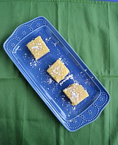 A blue platter sitting diagonally with three lemon bars, topped with powdered sugar, sitting on top of it on a green background.