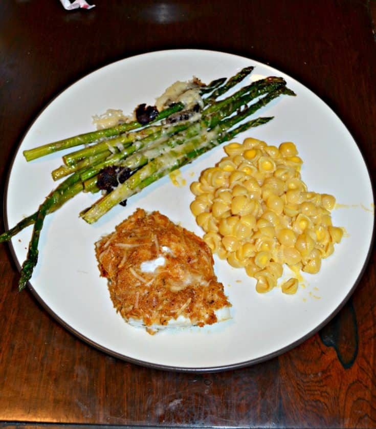 A white dinner plate with green asparagus in the upper left corner, yellow macaroni and cheese on the right side, and a piece of golden brown fish in the bottom left.