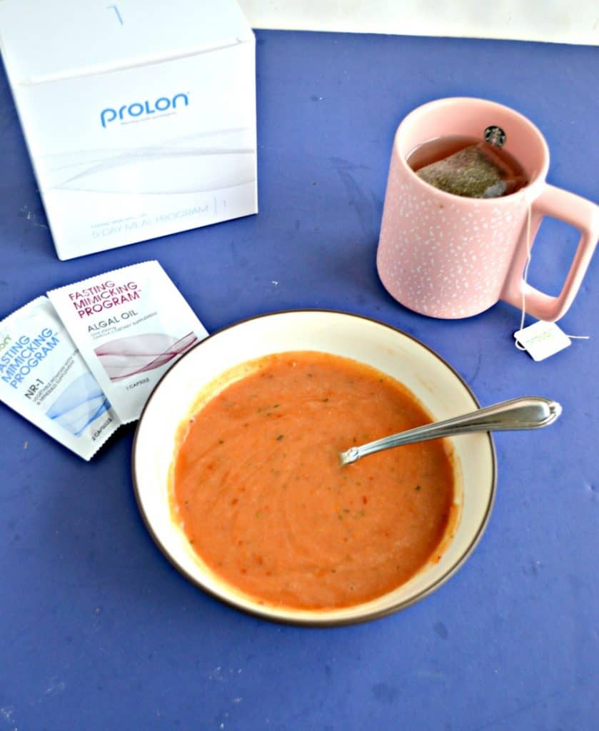 A blue background with a white bowl filled with orange tomato soup, a pink mug to the right with tea in it and a tea bag hanging out, two small white packets to the left of the bowl, and a white box to the upper left of the soup bowl.