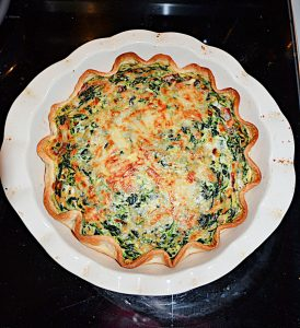 A pie pan with a Spinach Quiche that has a golden brown crust, the cheese on top has browned, and it's studded with spinach.