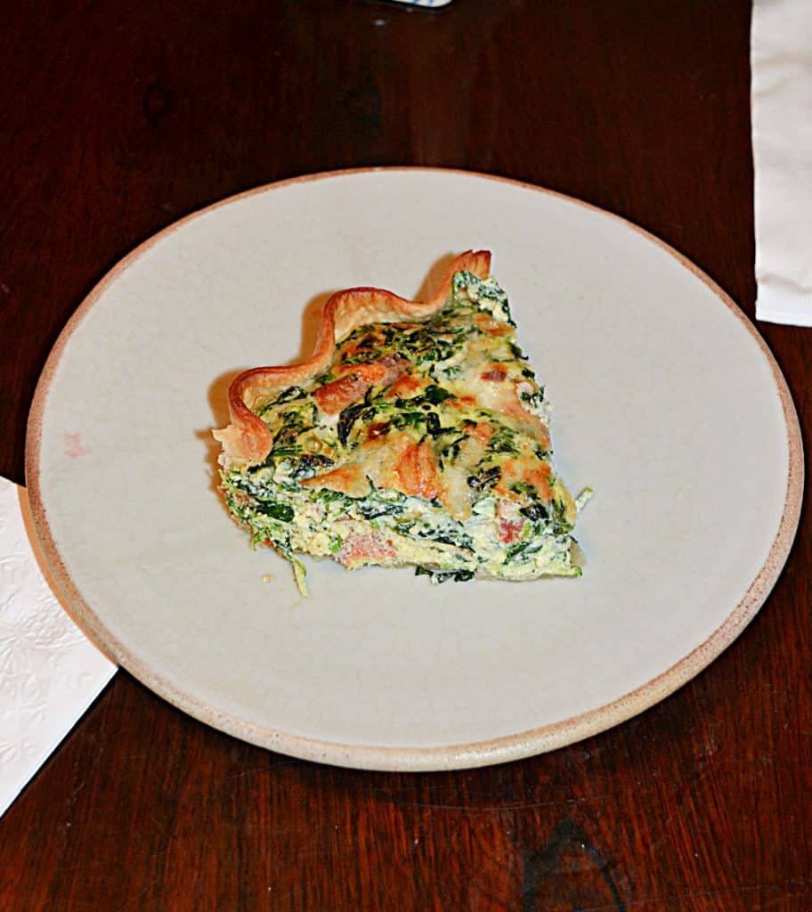A plate with a slice of Spinach and bacon quiche on it.
