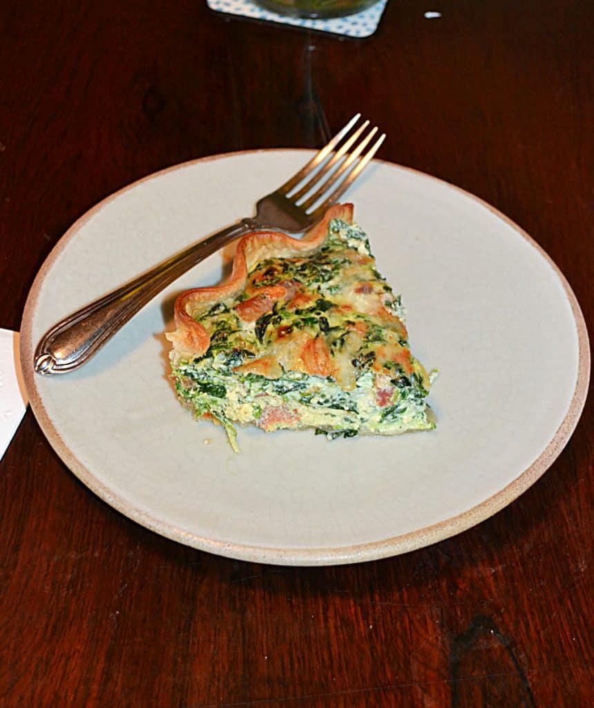 A plate with a slice of Bacon and Spinach quiche and a fork sitting on the plate behind the piece of quiche.