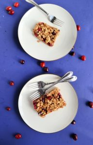 Two white plates each topped with a baked oatmeal square studded with red cranberries. The top plate has one fork on it and the bottom has two forks. There is a blue background with cranberries sprinkled on it.
