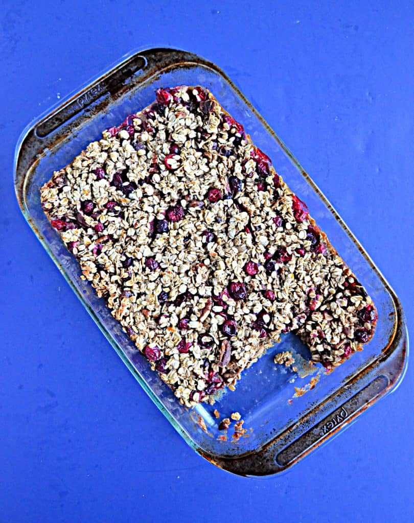 Baked Oatmeal studded with cranberries in a glass dish on a blue background.