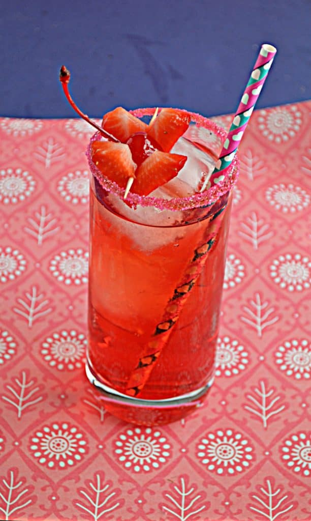 A tall glass filled with Cupid's Cocktail which is a bright red cocktail with a red sugared rim and two heart shaped strawberries and a paper straw on a pink background with a blue backdrop.