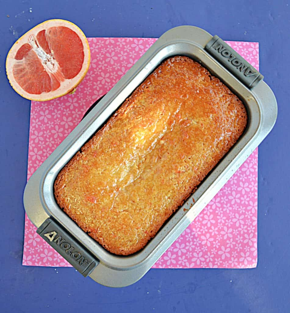 Grapefruit cake in a loaf pan with half a grapefruit in the background.