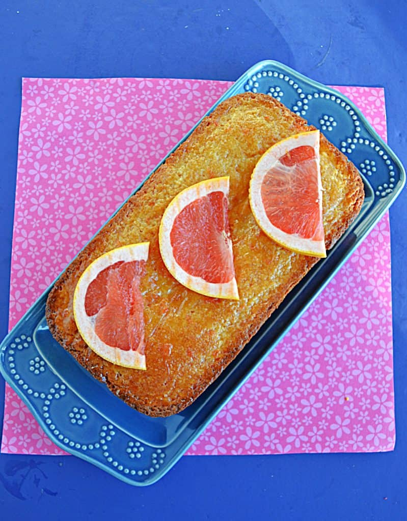 A loaf of grapefruit cake on a blue platter with three grapefruit slices on top.
