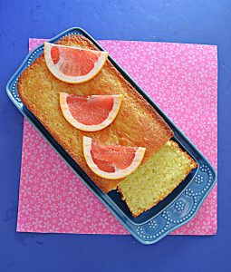 A loaf of grapefruit cake on a blue platter with three slices of grapefruit on top and a piece of the cake sliced off.