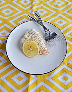 A large Meyer Lemon Scone on top of a white plate with a slice of lemon on top of it with two forks on the plate on a yellow and white background.