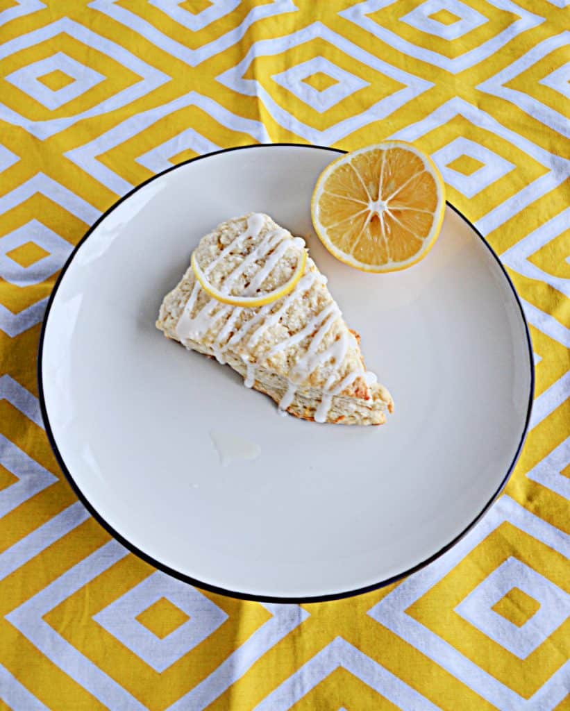 A large Meyer Lemon Scone on a white plate with a slice of lemon on a yellow and white background.