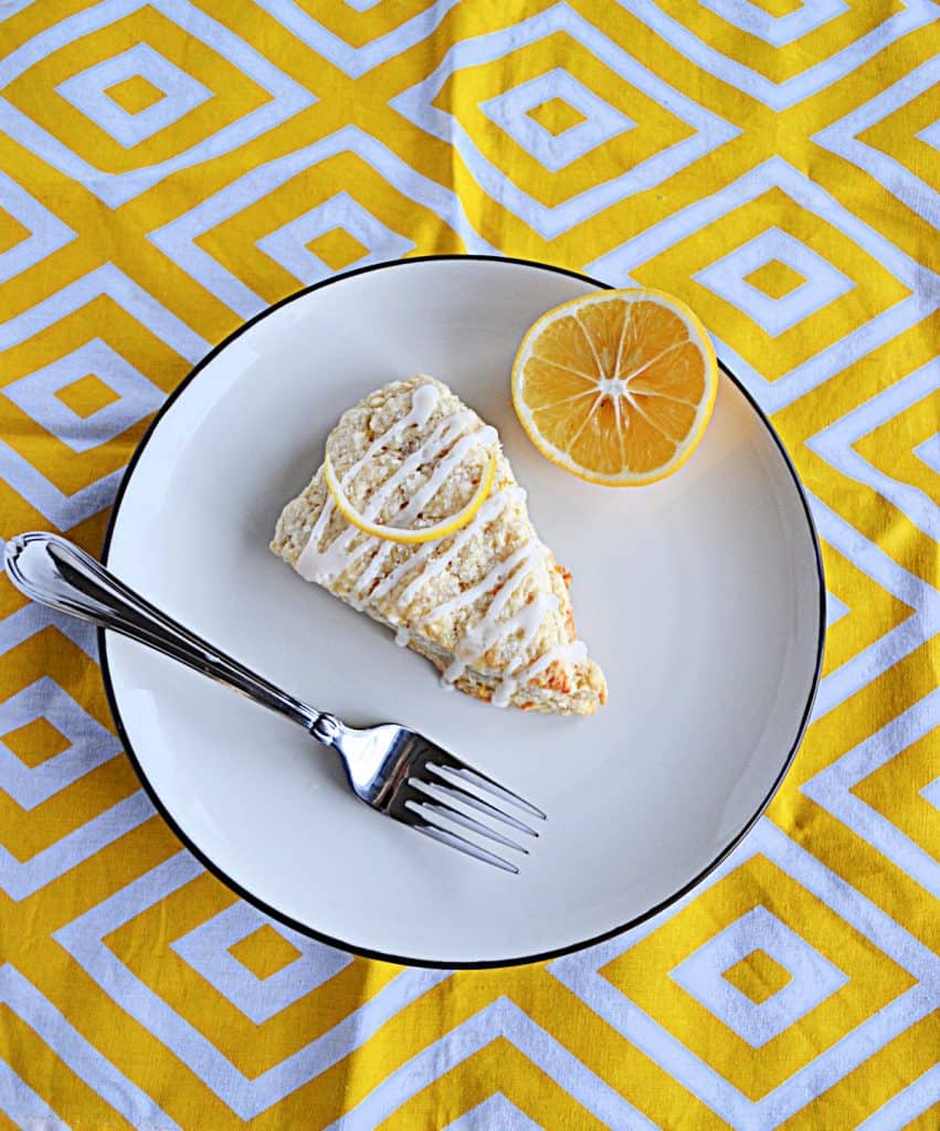 A large Meyer Lemon Scone on a white plate with a slice of lemon and a fork on the plate.
