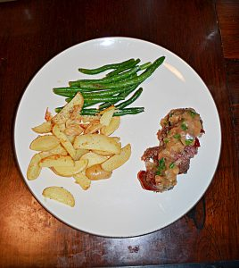 A white plate with a pile of steak fries, a pile of green beans, and a mini meatloaf sliced into four pieces with gravy on top.