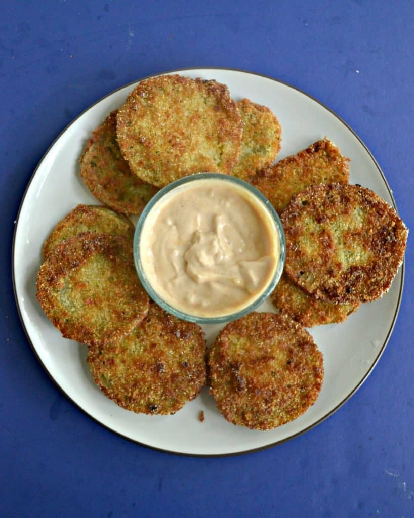A white plate piled high with fried green tomatoes and a glass bowl of light orange remoulade sauce in the middle on a blue background.
