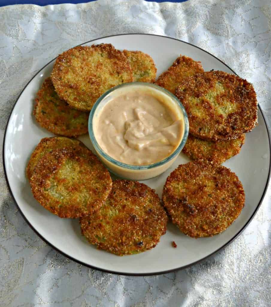 A white plate piled high with fried green tomatoes and a glass bowl of light orange remoulade sauce in the middle on a white background.