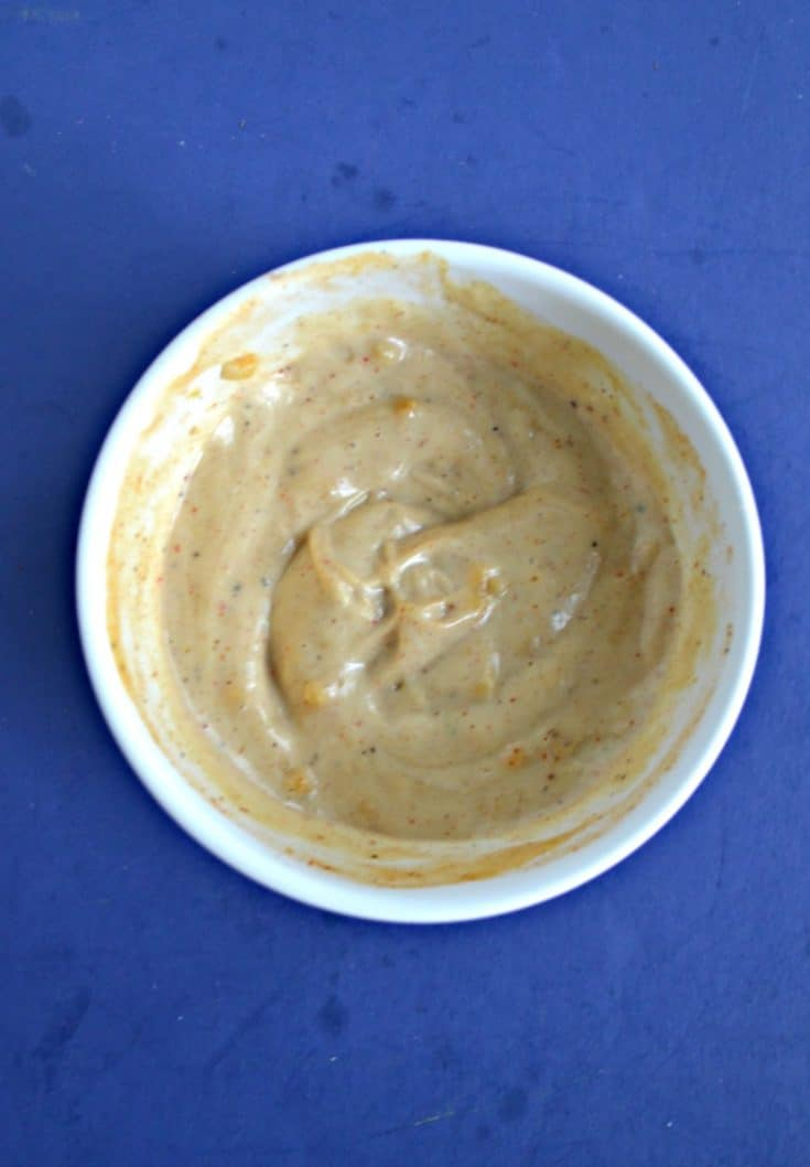 A white bowl filled with light orange remoulade sauce on a blue background.