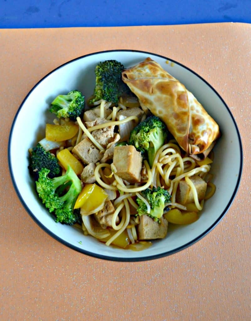A large bowl filled with tofu, broccoli, and noodles with a golden brown eggroll in the upper right corner all on an orange background.