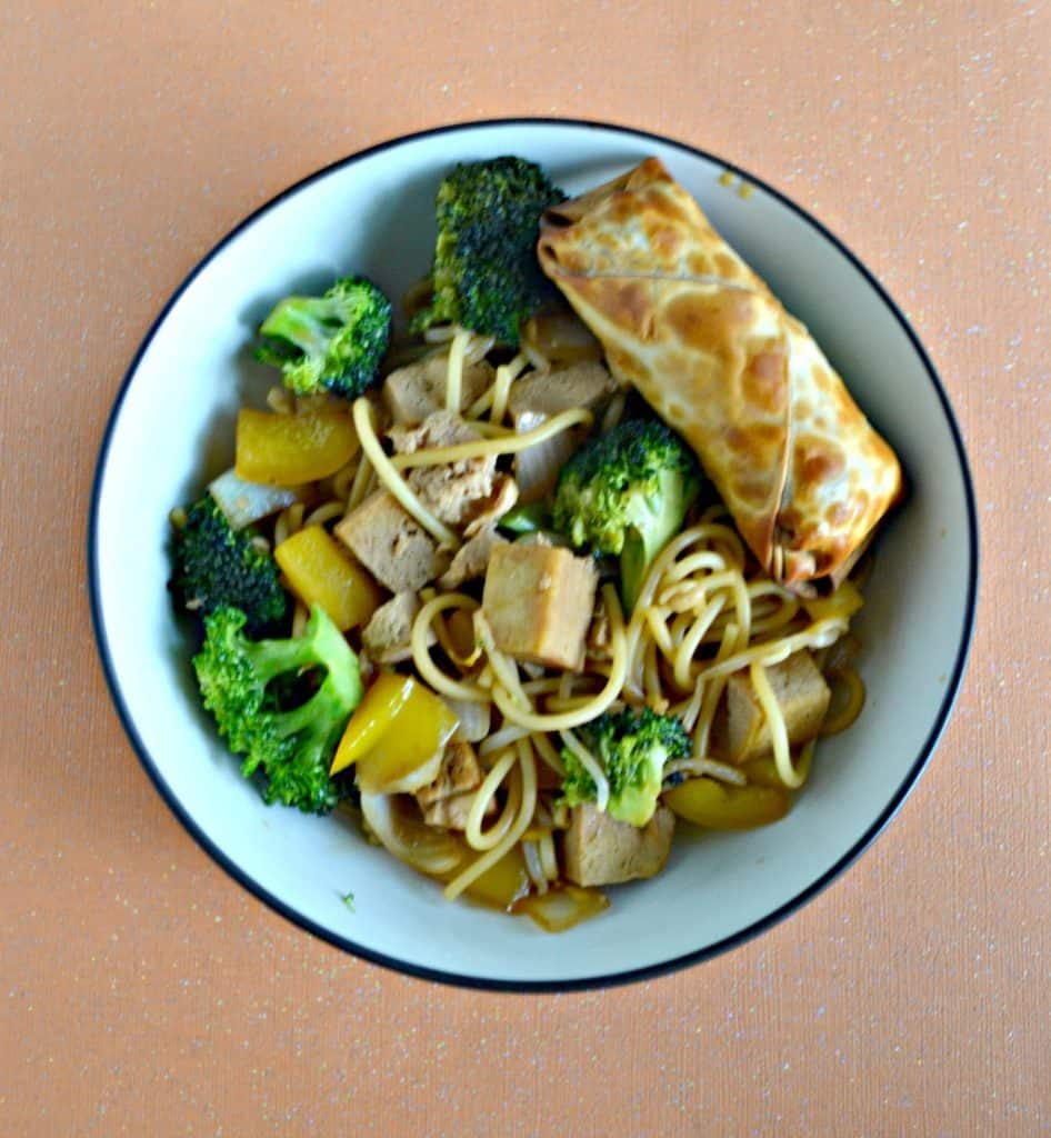 Overhead view of a large bowl filled with tofu, broccoli, and noodles with a golden brown eggroll in the upper right corner all on an orange background.