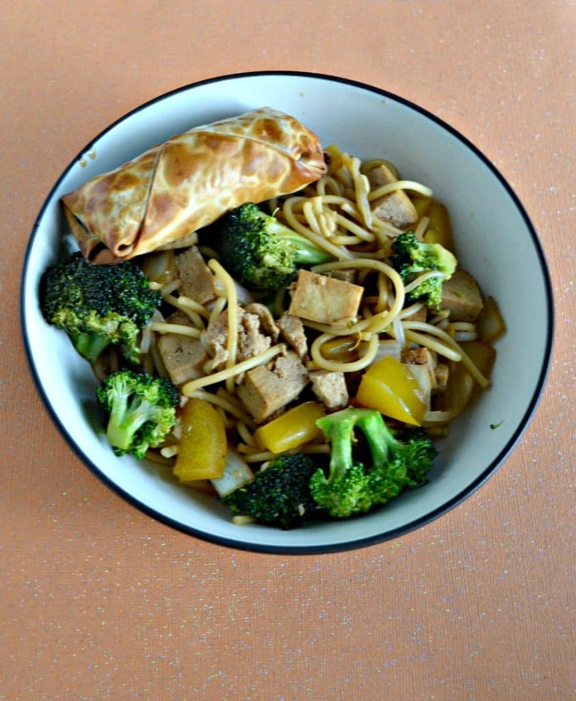 A large bowl filled with tofu, broccoli, and noodles with a golden brown eggroll in the upper left corner all on an orange background.