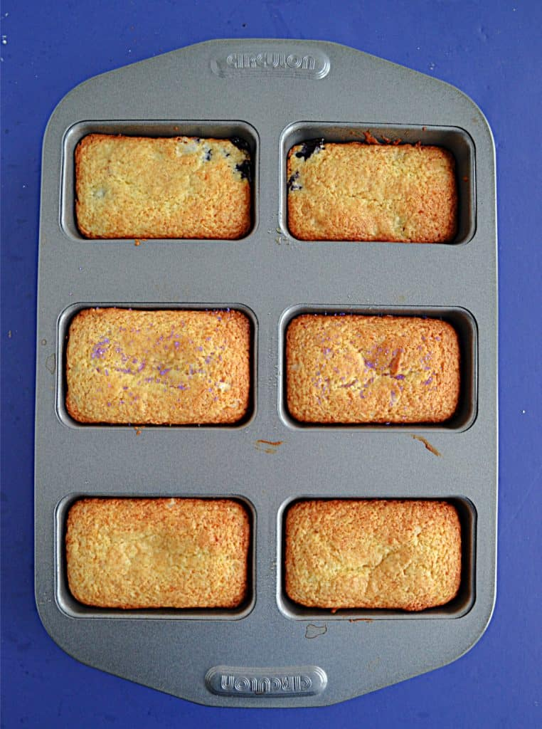 A mini loaf pan with six golden brown mini breads.