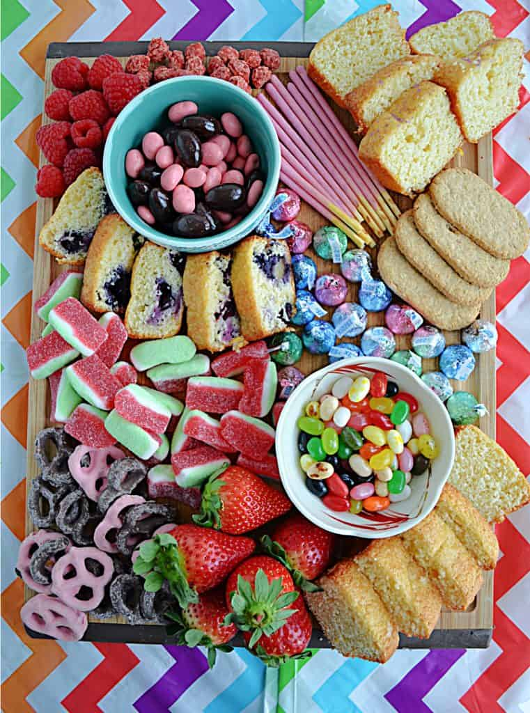 A large cutting board topped with colorful candies, cookies, quick breads, and nuts.