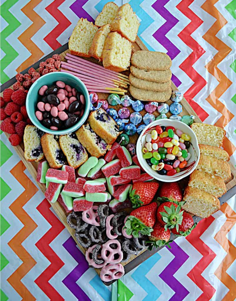 A colorful pastel dessert board filled with candies, cookies, fruits, and quick breads in Easter colors.